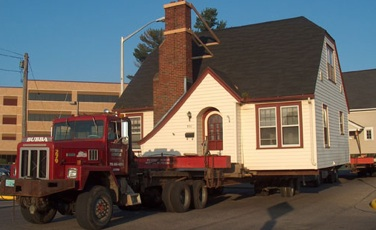 Willow makes moving easy! Adorable house being moved by big moving truck.